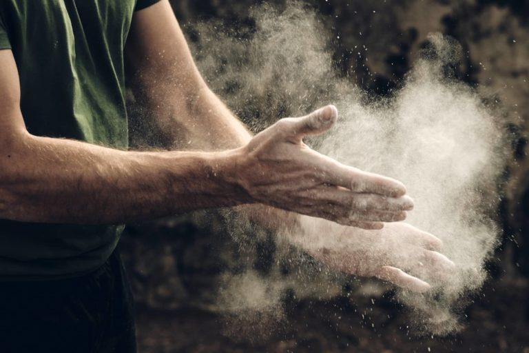 Boulderer klatscht in die Hände um das Magneisum zu verteilen