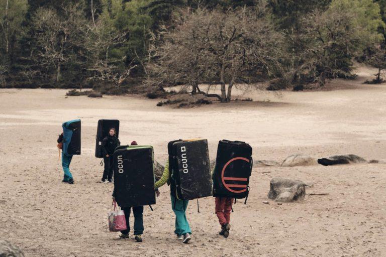 Boulderer/innen laufen mit Crashpads über den Sand in Fontainbleau